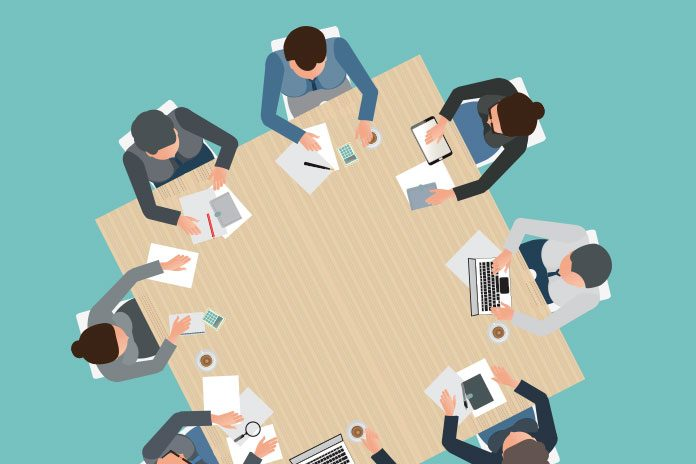 Image of business people sitting around a table to show The assessment centre process explained